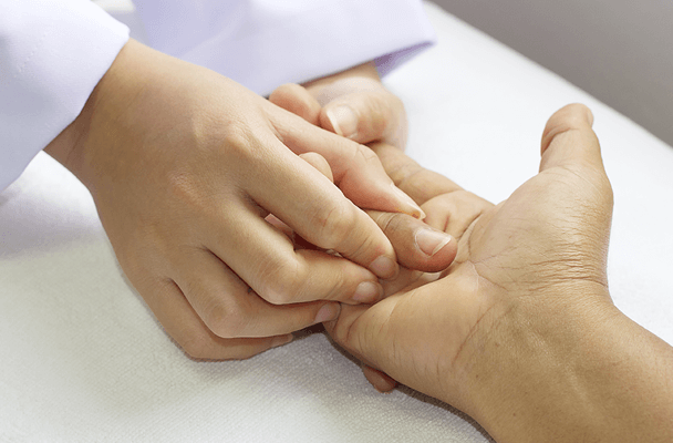 a hand therapist performing therapeutic hand exercises